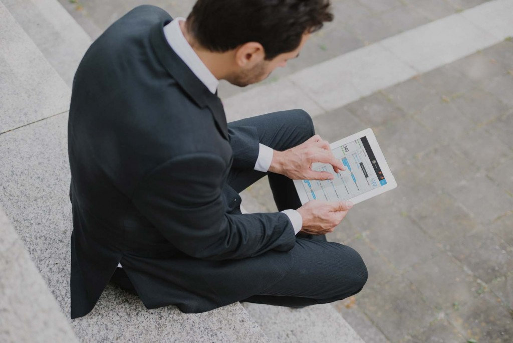 A suited men holding ipad using Gravity apps